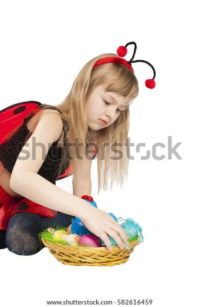 girl in costume ladybug with Easter eggs