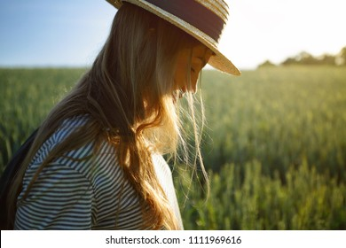 Girl in countryside green field, walking in straw hat, nature, close up, looking down