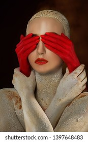 girl covered with clay with cracks and holds red hands that close her eyes