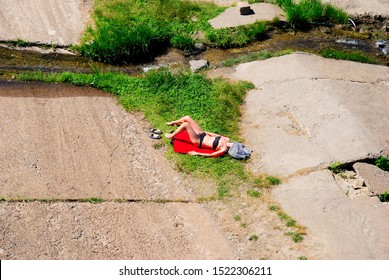 A girl with covered face sunbathing on the grass and concrete on the river bank