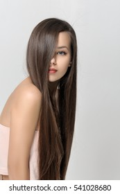 Girl covered her face with hair. Beautiful woman with bare shoulders has a clean well-groomed skin and long straight hair. Close-up portrait against a light gray background.