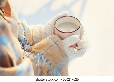 girl covered with plaid and in white knitted mittens holding in hands hot cocoa, tea with milk outdoors on snowy background. sweet cozy winter time. winter wonderland. winter still life