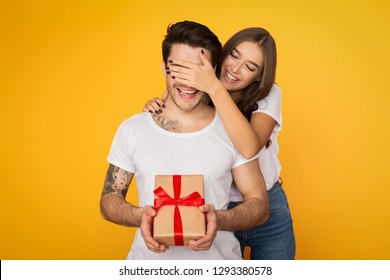 Girl covering her boyfriend eyes and giving him present on yellow background