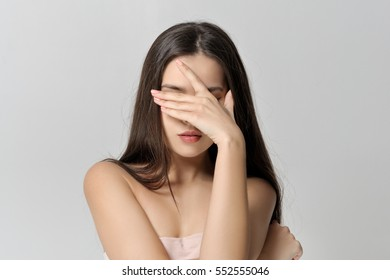 Girl covers her eyes with her hand. She has a clean well-groomed skin and long brown hair. Close-up portrait against a light gray background.