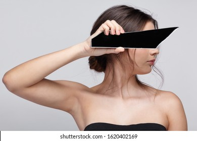 Girl covers her face with a shard of the mirror. Female with mirror shard in hand posing on gray background.