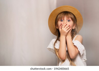 Girl covers her mouth with her hands, smoke indoors