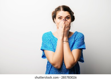 girl covers her mouth with her hands