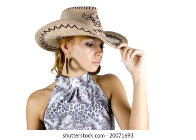Girl in cowboy hat - potrait. Young, pretty, blond girl wearing cowboy's hat, holding it by one hand.