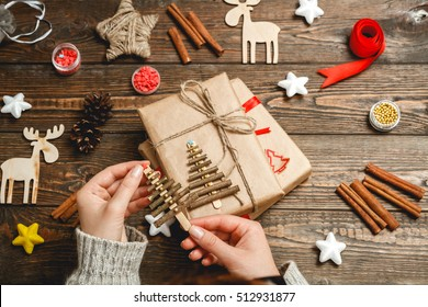 Girl in a cozy knit sweater creates a Christmas tree made of wooden shelves on dark wooden desk