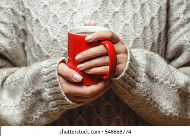The girl in a cozy knitted sweater drinking coffee from a red mug