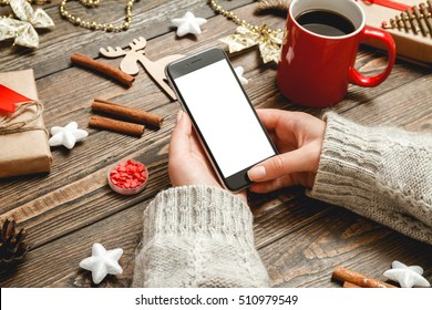 Girl in a cozy knitted sweater uses the phone while sitting at a table with Christmas accessories