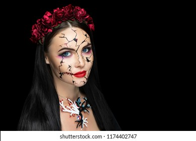 Girl with cracks in her face, conceptual art make up for Halloween party. Beautiful woman Broken doll puppet, dummy, poppet. Skin care old aging age. Vine marsala roses flowers wreath on head, jewelry