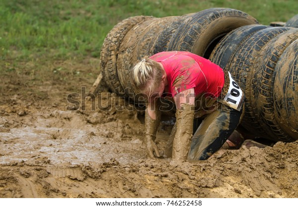 The girl creeps in the mud, emotionally overcoming the obstacle made of tires.