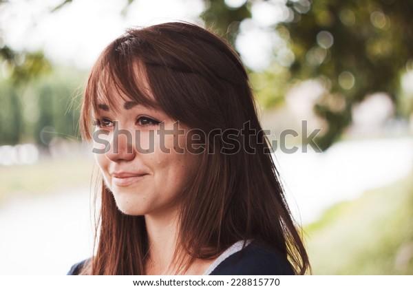 La ragazza piange e sorride. Occhi gonfi. Ritratto emotivo di bella bruna. Depressione, tristezza, solitudine