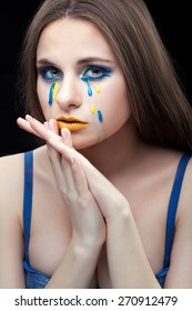 The girl crossed her arms and leaned his face. She tears on his face yellow blue.