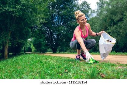 Girl crouching with bag picking up trash doing plogging