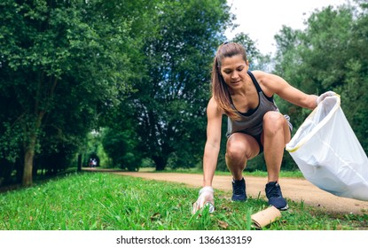 Girl crouching with garbage bag doing plogging