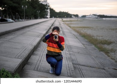 Girl crouching on concrete steps to take picture at sunset