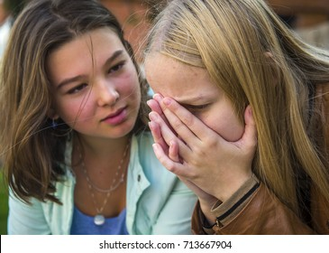 The girl is crying. The girlfriend consoles her