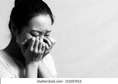 Girl crying with hand covering face