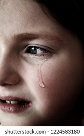 Girl crying with tears on face of cheek rolling down