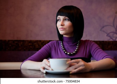 girl with cup of coffee in hands
