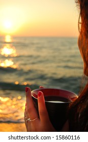 Girl with a cup of coffee looking the sea