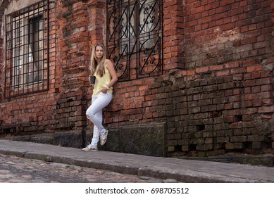 Girl with Cup of coffee the red brick wall