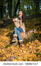girl with a cup of coffee sitting on a tree stump in autumn Park