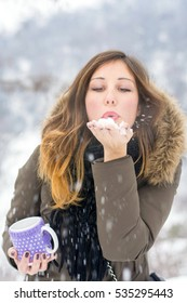 Girl with cup of tea on a cold snowy winter day
