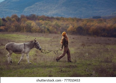 A girl with curly red hair in fashionable clothes in the style of Provence walk with cute donkey