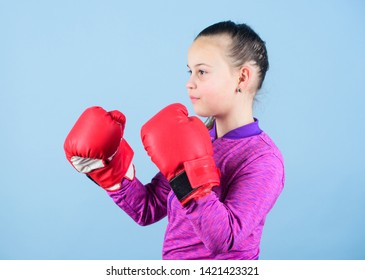 Girl cute boxer on blue background. Contrary to stereotype. Boxer child in boxing gloves. Confident teen. Enjoyment from sport. Female boxer. Sport upbringing. Boxing provide strict discipline.