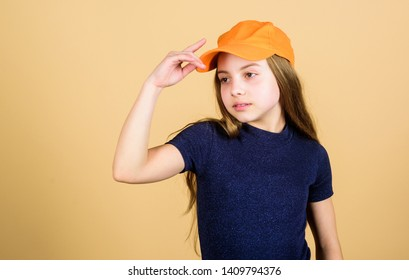Girl cute child wear cap or snapback hat beige background. Little girl wearing bright baseball cap. Modern fashion. Hat or cap. Stylish accessory. Kids fashion. Feeling confident with this cap.