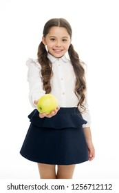 Girl cute pupil hold apple fruit stand on white background. Kid happy hold apple. School snack concept. Healthy nutrition diet. Apple vitamin snack. Child schoolgirl wear formal uniform hold apple.