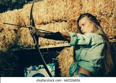 girl or cute woman, archer or hunter, with long hair shooting with bow and arrow on sunny day at archery target on hay bales. Concentrate, accuracy, ambition