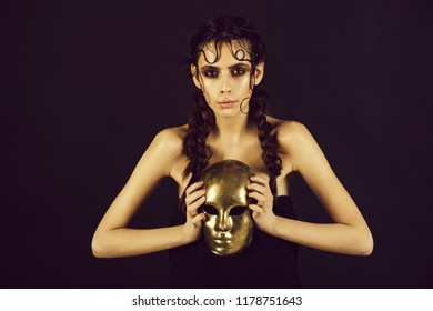 girl or cute woman holding carnival, golden, face mask on black background. Fashionable model with shining makeup and braids, plaited hair, hairstyle. Masquerade. Holiday, celebration. Theatre