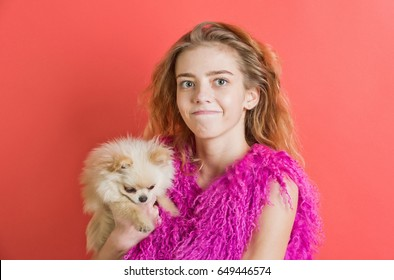 girl or cute woman with natural blond, long, wavy hair smiling with closed mouth on young face, no makeup in pink feather boa and small, spitz dog, pet in hands on red wall. Fashion, friendship