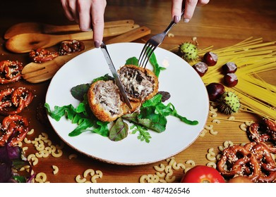 Girl cuts a knife appetizing cutlet stuffed with cheese close up. fried meat ball cutlet of veal on a plate on wooden background and vegetables