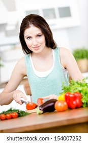 Girl cuts vegetables for salad sitting at the kitchen table