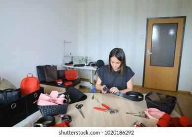Girl cutting piece of leather of necessary form for making women bag. Young woman interested in making handbags and decided to please friend with handmade accessory. Black-haired lady wearing gr