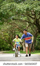 Girl cycling, father running alongside her