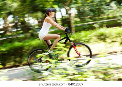 Girl cycling in the park, it's a sunny summer day. Motion blured image.