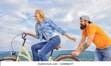 Girl cycling while man support her. Support helps believe in yourself. Feel impulse to start moving. Woman rides bicycle sky background. Push and promoting. Impulse to move. Man pushes girl ride bike.
