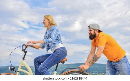 Girl cycling while man support her. Feel impulse to start moving. Woman rides bicycle sky background. Push and promoting. Impulse to move. Man pushes girl ride bike. Support helps believe in yourself.