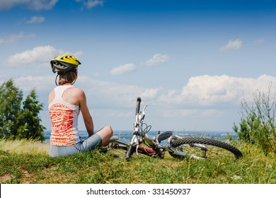 Girl cyclist with bycicle relax in the meadow