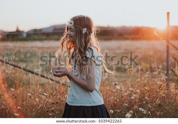 girl in daisy flower field at sunset