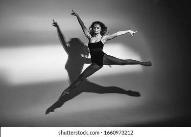 The girl is a dancer, a blonde in a black body, dances in the light of a searchlight, makes waved arms and legs, jumps. black and white photo
