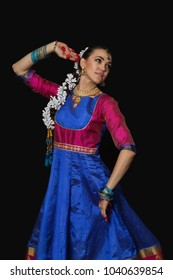 Girl dancer of Indian dances. A woman in an Indian suit. Portrait on a black background.
