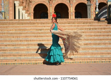 The girl dances flamenco with a green dress and cloak