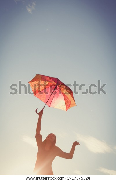 The girl dances with an umbrella in her hands against the clear sky, the picture is tinted in retro colors and a vignette is added